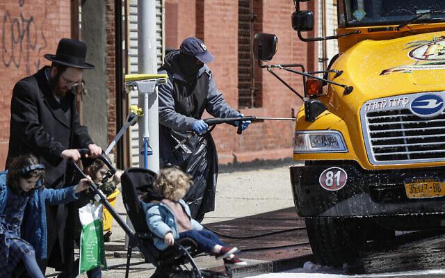 Un employé portant un équipement de protection individuelle lave un bus scolaire qui dessert une communauté juive ultra-orthodoxe dans le quartier de Brooklyn à New York, le 27 mars 2020. (AP Photo/John Minchillo)