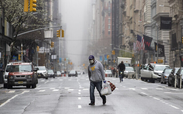 Un homme portant un masque facial traverse le milieu de la 5e Avenue dans le Midtown Manhattan de New York, le 29 mars 2020. (AP Photo/Mary Altaffer)