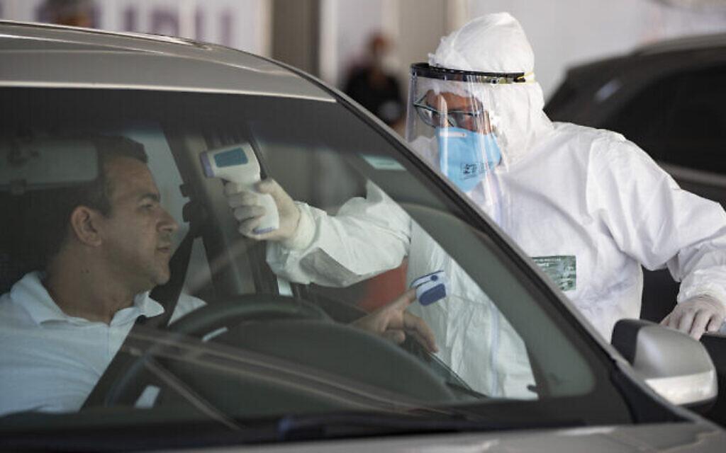 Le personnel médical contrôle les personnes à l'intérieur de leur voiture pour savoir si elles présentent des symptômes du COVID-19 à Guarulhos, dans la banlieue de Sao Paulo, au Brésil, le lundi 30 mars 2020. (Crédit : AP Photo/Andre Penner)