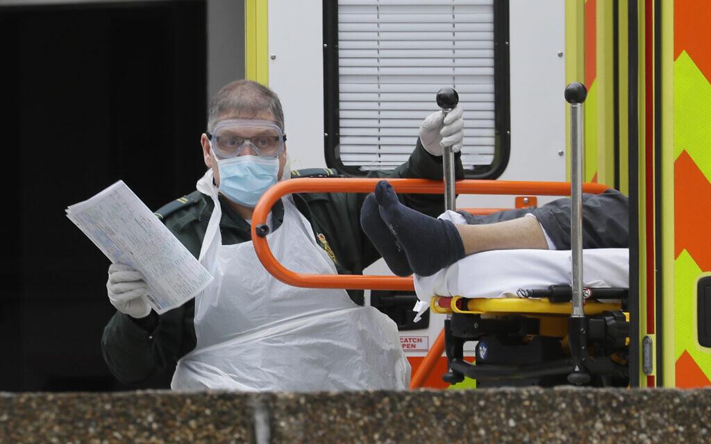 Un patient est sorti d'une ambulance à son arrivée au  St Thomas' Hospital, l'un des hôpitaux dans la ligne de front de la bataille contre le coronavirus à Londres, le 31 mars 2020 (Crédit : AP Photo/Kirsty Wigglesworth)