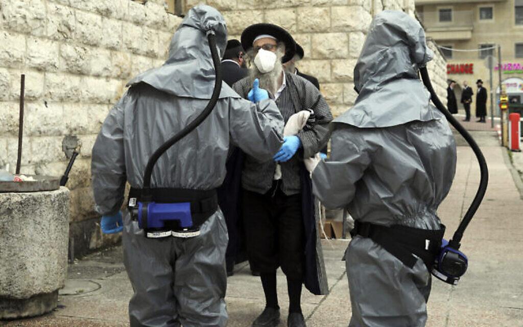 Un juif orthodoxe s'entretient avec des membres de Hevra Kadisha venus enlever le corps d'une personne décédée du coronavirus à Jérusalem, le 1er avril 2020. (Crédit : AP Photo/Mahmoud Illean)