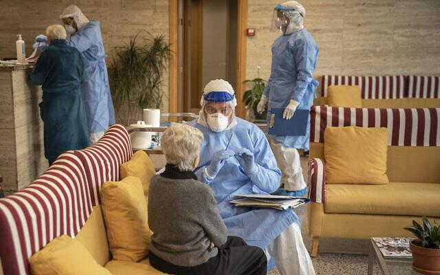 Photo d'illustration : Un aide-soignant parle à une personne âgée avant un dépistage dans une maison de retraite de Barcelone, en Espagne, le 1er avril 2020 (Crédit : AP Photo/Santi Palacios)