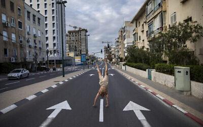 Un Israélien fait l'équilibre dans une rue vide de Tel Aviv pendant le confinement imposé par le coronavirus, le 8 avril 2020. (AP Photo/Oded Balilty)