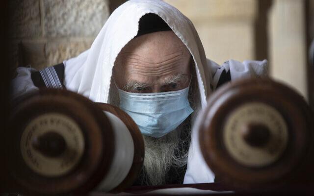 Un homme juif porte un masque sur le visage pour éviter la propagation du coronavirus alors qu'il lit un rouleau de Torah au mur Occidental, dans la Vieille Ville de Jérusalem, le 10 avril 2020 (Crédit : AP Photo/Sebastian Scheiner)