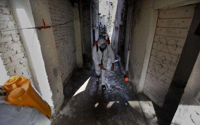 Des bénévoles d'une organisation caritative désinfectent les allées d'un quartier pauvre afin d'endiguer la propagation du virus à Islamabad au Pakistan, le mercredi 15 avril 2020. (AP Photo/Anjum Naveed)
