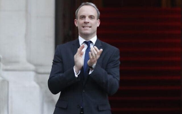 """Le ministre britannique des Affaires étrangères Dominic Raab applaudit au Foreign Office à Londres lors des """"Clap for our Carers"""" applaudissement hebdomadaires pour nos soignants, à Londres, le 23 avril 2020. (AP Photo/Frank Augstein/pool)"""