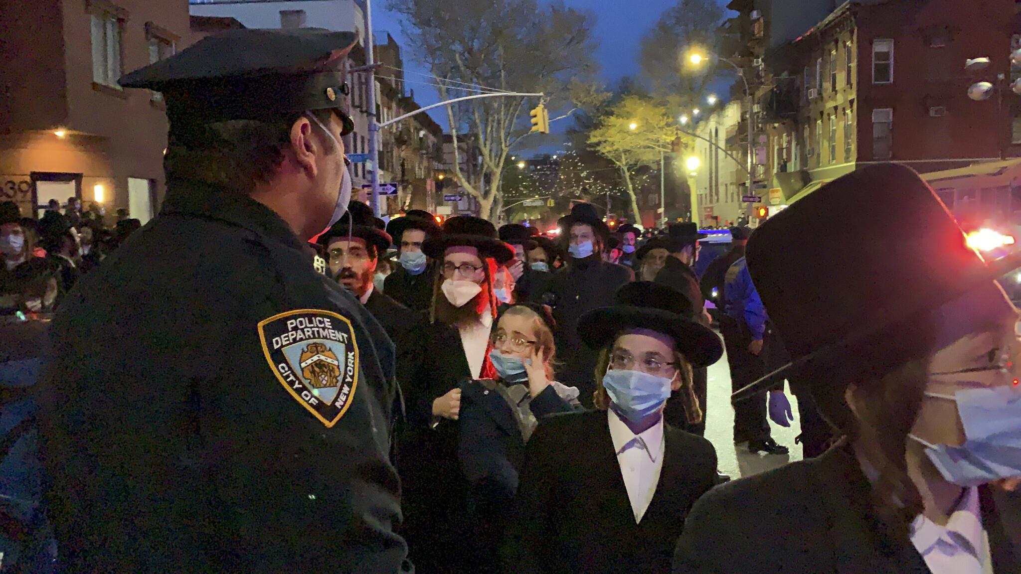 Un officier de police de la ville de New York monte la garde alors que des centaines de personnes se rassemblent à Brooklyn à New York, le 28 avril 2020, pour assister aux funérailles du rabbin Chaim Mertz, décédé du coronavirus. (Crédit : Peter Gerber, via AP)