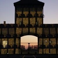 Des plaques mémorielles virtuelles sont projetées sur les portes d'Auschwitz-Birkenau à l'occasion de Yom HaShoah, le 20 avril 2020. (Crédit : Marcin Kozlowski/Marche des vivants)