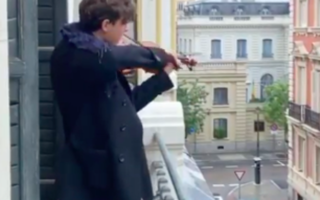 Un violoniste interprète l'hymne national israélien 'hatikva' pour ses voisins pendant la confinement à Madrid. (Capture d'écran : YouTube)