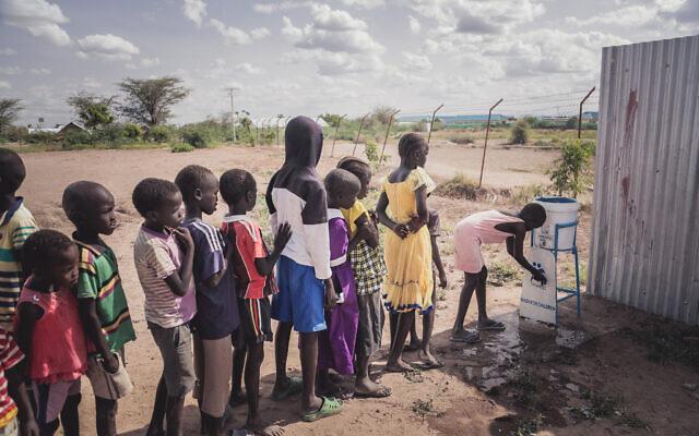 Illustration : Des enfants utilisent une structure d'eau potable mise en place par IsraAID à Kakuma, au Kenya. (Crédit : Lior Sperandeo/IsraAID)