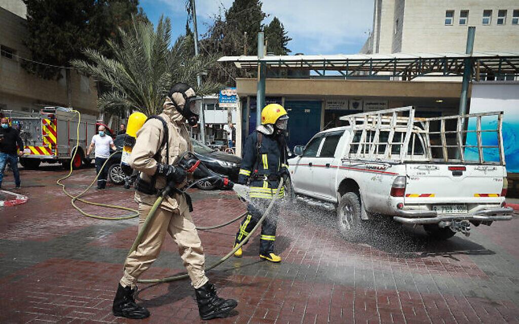 Des employés municipaux palestiniens désinfectent le parking d'un hôpital dans la ville de Ramallah en Cisjordanie, le 12 mars 2020. (Flash90)