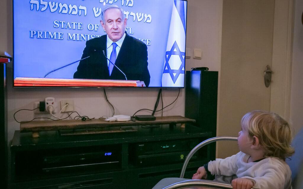 Un enfant israélien regarde le Premier ministre israélien Benjamin Netanyahu lors d'une conférence de presse en direct sur les nouvelles restrictions gouvernementales dans le cadre de la lutte contre la pandémie de coronavirus, le 19 mars 2020. (Crédit : Chen Leopold / Flash90)