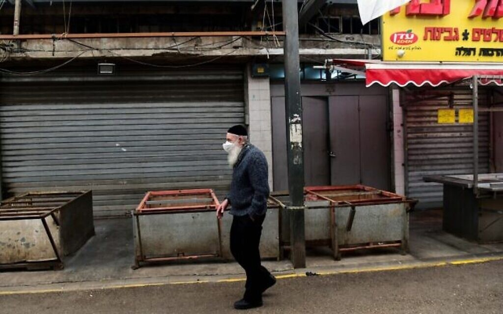 Photo d'illustration : Un homme portant un masque facial marche dans le marché vide de Ramla, le 23 mars 2020 (Crédit : Flash90)