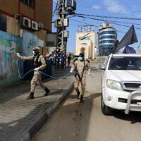 Les membres de l'aile militaire du Jihad islamique palestinien, les Brigades Al-Quds, désinfectent les rues de Rafah, dans le sud de la bande de Gaza, le 26 mars 2020 (Crédit : Abed Rahim Khatib/Flash90)