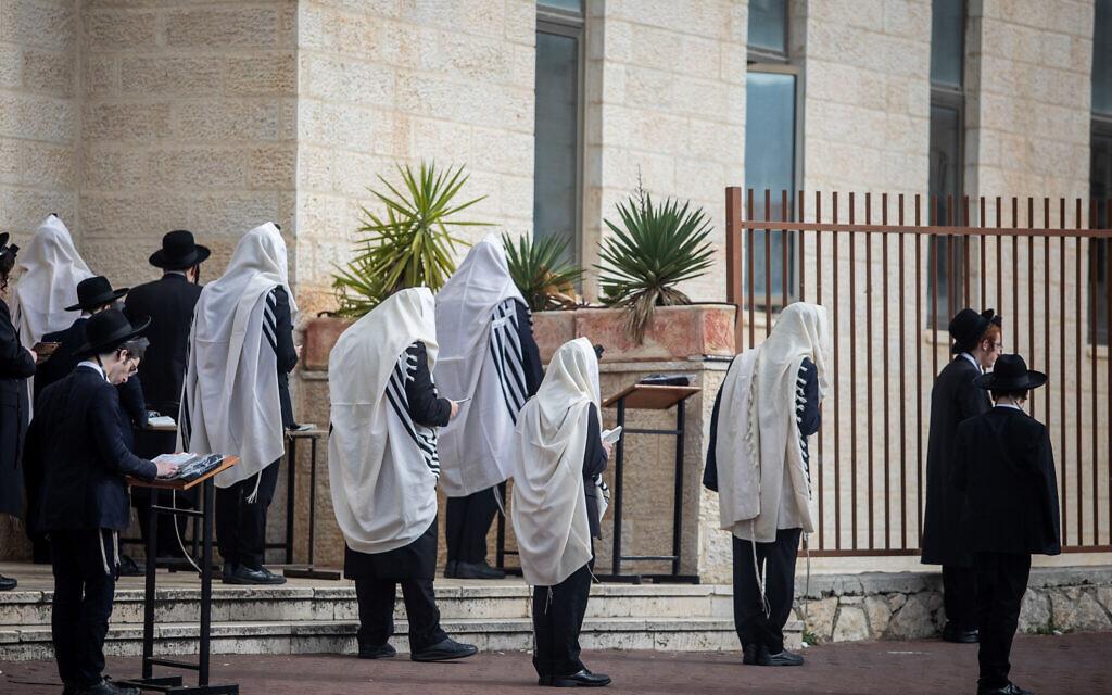 Des Juifs prient aux abords d'une synagogue dans la ville de Beitar Illit, en Cisjordanie, le 29 mars 2020 (Crédit : Aharon Krohn/Flash90)