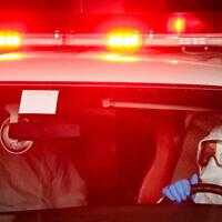 Des travailleurs du Magen David Adom portant des vêtements de protection évacuent un homme suspecté d'être atteint de coronavirus vers l'hôpital Shaarei Tsedek à Jérusalem, 30 mars 2020. (Yossi Zamir/Flash90)