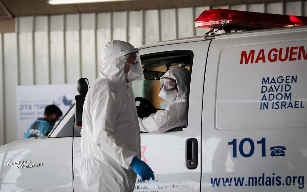 Des agents du Magen David Adom portant des vêtements de protection comme mesure préventive contre le coronavirus, vus lors de l'évacuation d'un homme suspecté de coronavirus à l'hôpital Shaare Zedek de Jérusalem, le 30 mars 2020. (Yossi Zamir/Flash90)