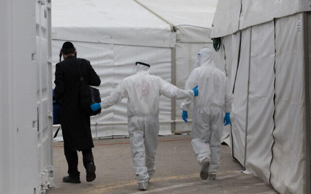 Des employés du Magen David Adom et une équipe médicale de Shaare Tzedek, portant des équipements de protection contre le coronavirus, aux abords de la nouvelle unité de l'hôpital Shaare Zedek à Jérusalem, le 2 avril 2020 (Crédit :  Nati Shohat/Flash90)