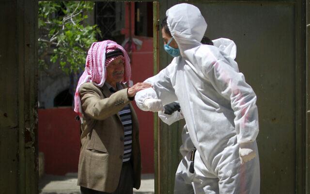 Des travailleurs palestiniens nettoient les rues et les maisons à Naplouse, en Cisjordanie, dans le cadre de la lutte contre le coronavirus le 3 avril. (Crédit :  Nasser Ishtayeh/Flash90)