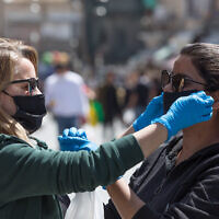 Des femmes s'entraident pour revêtir des masques au marché de Mahane Yehuda (Nati Shohat/Flash90)