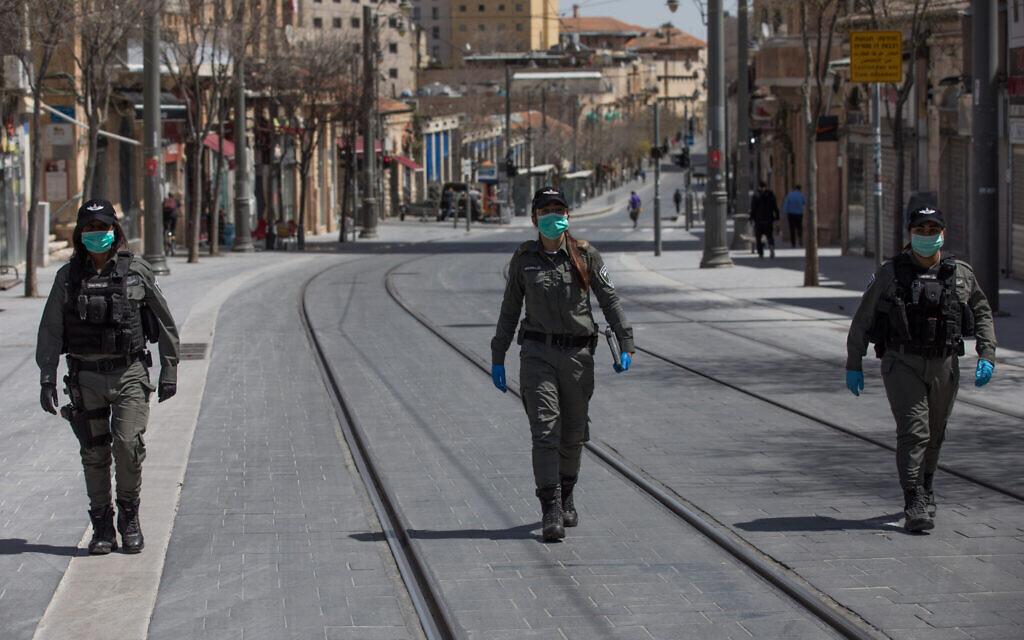 La police des frontières israélienne, le visage masqué, lors d'une patrouille dans le centre de Jérusalem, vérifie que la population respecte les ordres du gouvernement sur le confinement partiel imposé par la crise du coronavirus, le 3 avril 2020 (Crédit : Nati Shohat/Flash90)