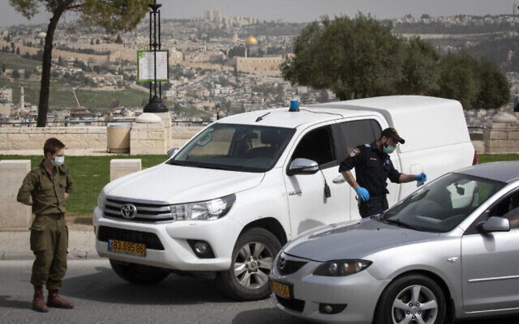 Des policiers et des soldats israéliens à un poste de contrôle temporaire à Jérusalem, pour vérifier que les gens ne désobéissent pas aux ordres du gouvernement visant à empêcher la propagation du coronavirus, 5 avril 2020 (Crédit : Olivier Fitoussi / Flash90)