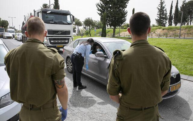 """Des policiers et des soldats israéliens à un """"point de contrôle"""" temporaire à Jérusalem, pour contrôler que les gens ne désobéissent pas aux consignes du gouvernement sur un confinement partiel afin d'empêcher la propagation du coronavirus, le 5 avril 2020. (Olivier Fitoussi/Flash90)"""