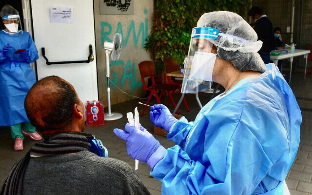 Les personnels médicaux en combinaison de protection sur un site de dépistage du coronavirus dans le sud de Tel Aviv, le 6 avril 2020 (Crédit : Avshalom Sassoni/Flash90)