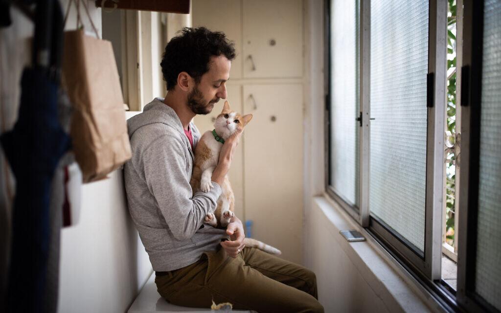 Un homme caresse son chat assis devant la fenêtre de son appartement pendant la quarantaine nationale, à Jérusalem, le 18 mars 2020. (Hadas Parush/Flash90)