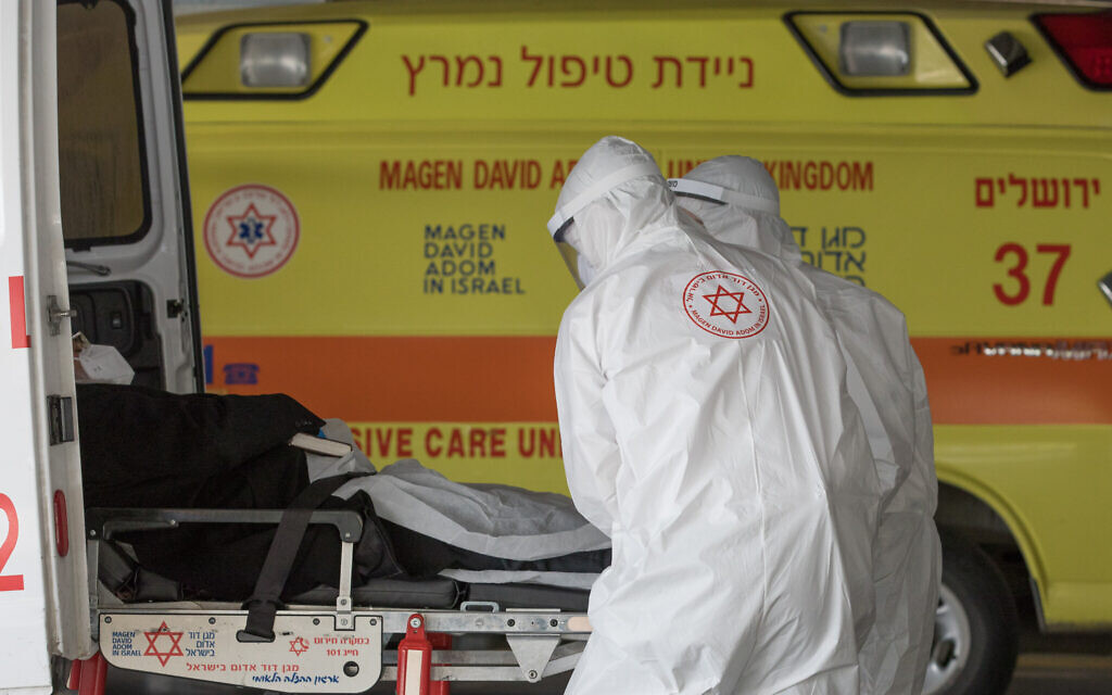 Photo d'illustration : Des médecins du Magen David Adom avec des combinaisons de protection contre le coronavirus pendant le transfert d'un malade à l'hôpital Shaare Zedek, à Jérusalem, le 6 avril 2020 (Crédit : Nati Shohat/Flash90)