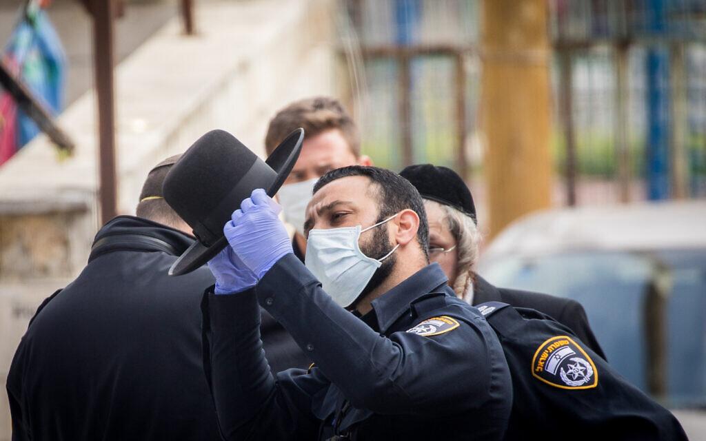 Des agents de police ferment des synagogues et distribuent des amendes à des ultra-orthodoxes dans le quartier de Bukharim à Jérusalem, le 6 avril 2020 (Crédit : Yonatan Sindel/Flash90)