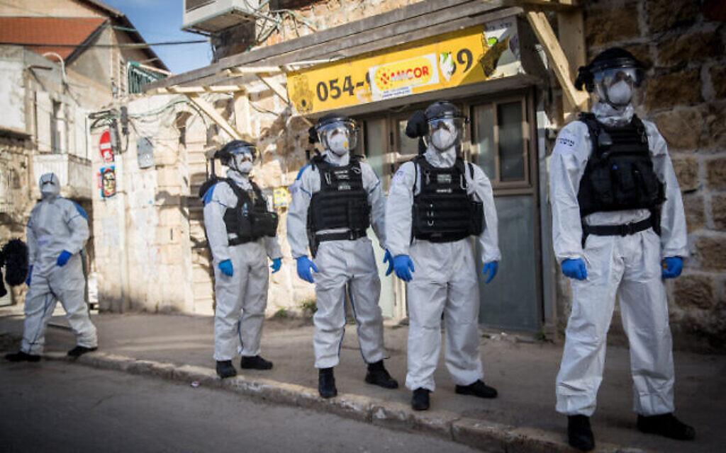 Des agents de police israéliens en combinaison de protection dans le quartier ultra-orthodoxe de Mea Sharim à Jérusalem, le 6 avril 2020. (Crédit : Yonatan Sindel/Flash90)