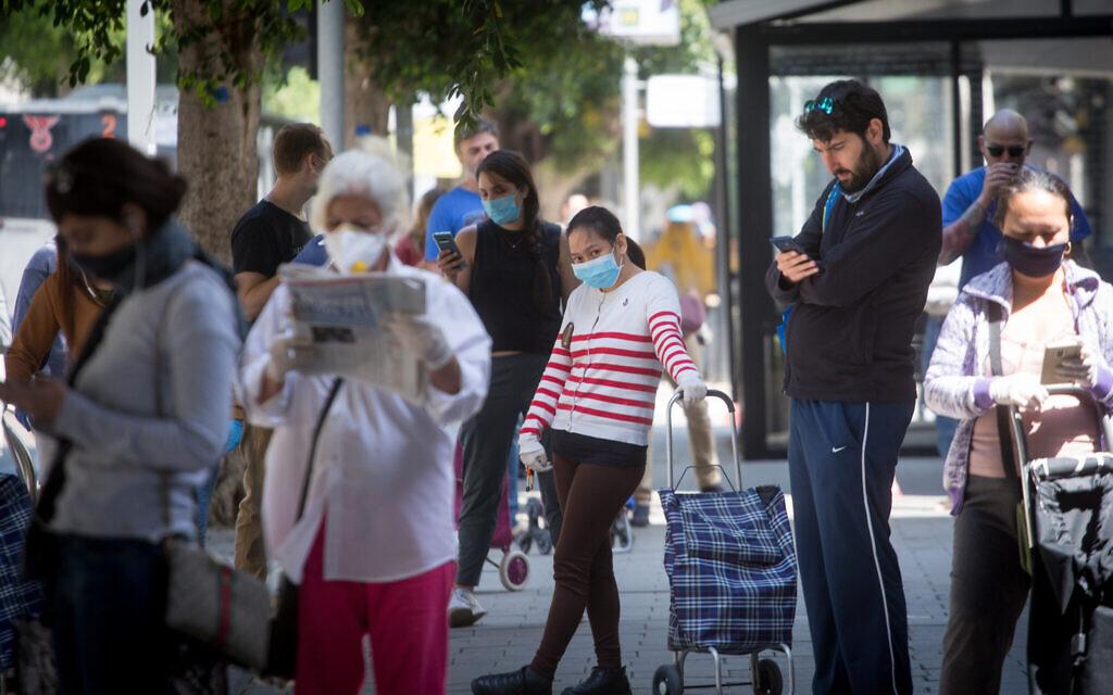 Des clients attendent devant un supermarché à Tel Aviv, le 7 avril 2020. (Crédit : Miriam Alster/Flash90)