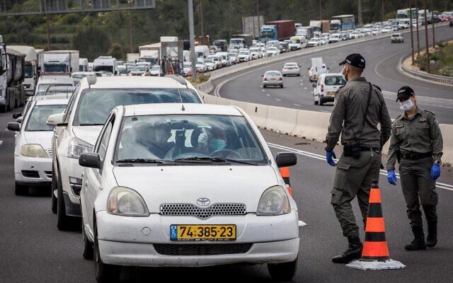La police contrôle les conducteurs à un point de contrôle temporaire sur la route 1 à l'extérieur de Jérusalem, pour vérifier que les gens respectent les ordres du gouvernement concernant un confinement partiel pour empêcher la propagation du coronavirus. (Nati Shohat/Flash90)