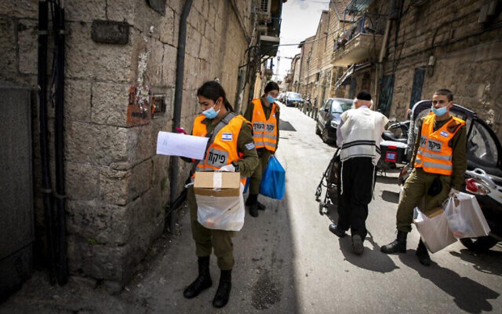 Des soldats du commandement intérieur distribuent des colis alimentaires aux personnes âgées obligées de rester confinées en raison de la crise du coronavirus avant la fête juive de Pessah, dans un quartier haredim de Jérusalem, le 7 avril 2020 (Crédit : Olivier Fitoussi/Flash90)