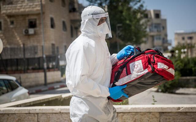 Des employés du Magen David Adom en combinaison de protection contre le coronavirus se rendent chez un malade présumé à Jérusalem, le 14 avril 2020 (Crédit : Yonatan Sindel/Flash90)