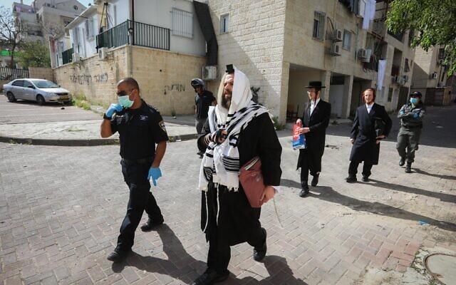 Les officiers de police ferment les synagogues et distribuent des amendes aux Juifs ultra-orthodoxes à Beit Shemesh, le 16 avril 2020 (Crédit : Yaakov Lederman/Flash90)