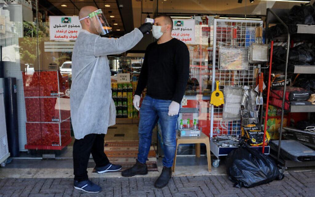 Un employé contrôle la température d'un client à l'entrée d'un magasin de la ville arabe israélienne de Deir al-Asad, le 18 avril 2020 (Crédit : Basel Awidat/Flash90)