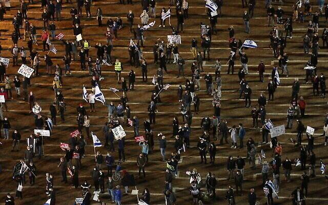 """Gardant entre eux une distance de deux mètres, des milliers de manifestants assistent à une manifestation des """"drapeaux noirs"""" à Tel Aviv, le 25 avril 2020 (Crédit : Miriam Alster/Flash90)"""