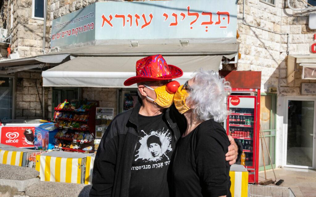 Un couple d'Israéliens, masqués, s'embrassasse à Jérusalem, le 26 avril 2020. (Crédit : Olivier Fitoussi/Flash90)