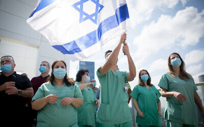 Le personnel médical acclame une équipe de voltige de l'armée de l'air israélienne survolant l'hôpital Ichilov à Tel Aviv, lors du 72e anniversaire de l'indépendance d'Israël, Yom HaAtsmaout, le 29 avril 2020. (Miriam Alster/Flash90)