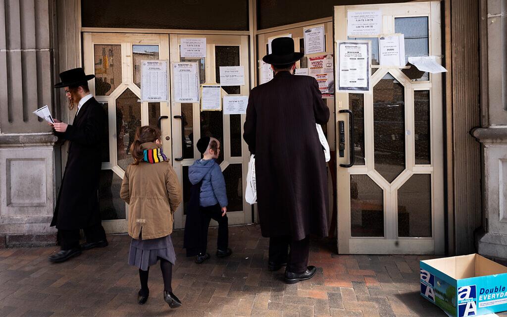 Un homme s'arrête pour lire des annonces affichées sur les portes d'une synagogue dans le quartier de Williamsburg à Brooklyn, New York, le 7 avril 2020. (Crédit : AP/Mark Lennihan)