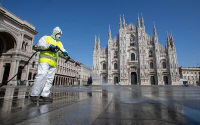 Un employé désinfecte la place Duomo dans le centre de Milan, en Italie, le 31 mars 2020 (Crédit : AP/Luca Bruno)