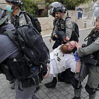 La police arrête un homme ultra-orthodoxe alors qu'elle ferme une synagogue dans le quartier de Mea Shearim à Jérusalem pour non-respect des directives d'urgence visant à endiguer le coronavirus, le 30 mars 2020. (Ahmad Gharabli/AFP)