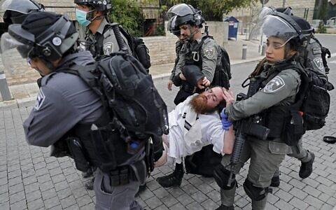 La police arrête un homme ultra-orthodoxe alors qu'elle ferme une synagogue dans le quartier de Mea Shearim à Jérusalem pour non-respect des directives visant à endiguer l'épidémie de Covid-19, le 30 mars 2020. (Ahmad Gharabli/AFP)