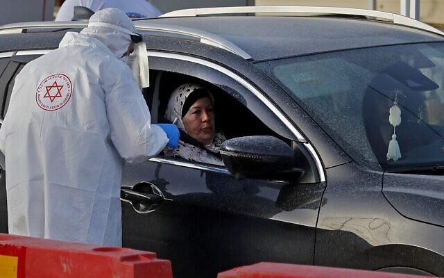 Un agent du service médical d'urgence Magen David Adom réalise un prélèvement dans le cadre d'un test de dépistage du coronavirus sur un site en drive-in à Tamra, dans le nord d'Israël, le 31 mars 2020. (Crédit : Ahmad GHARABLI / AFP)
