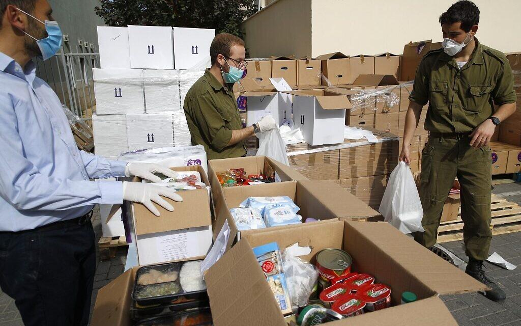 Des soldat israéliens portent des cartons de nourritures et d'autres produits de première nécessité qu'ils vont distribuer aux seniors placé à l'isolement dans la ville côtière de Bat Yam, le 7 avril 2020.  (Photo par JACK GUEZ / AFP)