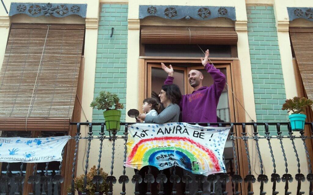 """Une famille applaudit depuis son balcon, avec une banderole où l'on peut lire """"Tout ira bien"""" le 9 avril 2020 à Valence en Espagne, lors du confinement national pour lutter contre la propagation du COVID-19. (Photo par Jose Jordan / AFP)"""