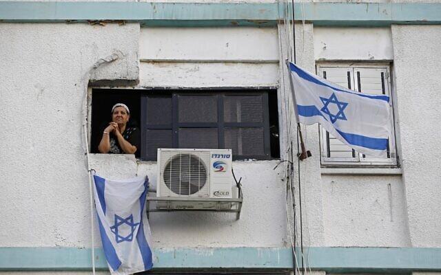 Une femme israélienne observe la rue depuis la fenêtre de sa maison dans un bâtiment décoré par des drapeaux nationaux dans la ville du sud d'Ashkelon, le 27 avril 2020. (MENAHEM KAHANA / AFP)