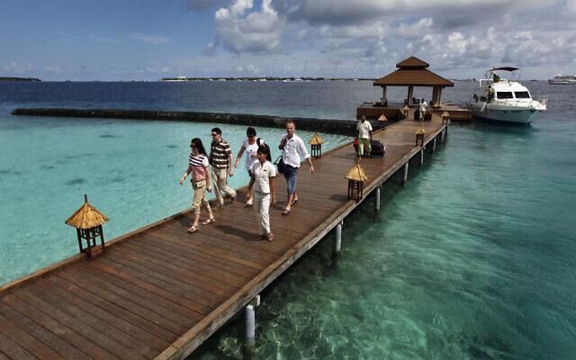Des touristes étrangers arrivent dans une résidence de vacances sur l'île de Kurumba aux Maldives, le 12 février 2012. (AP Photo/ Gemunu Amarasinghe, File)